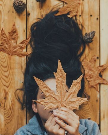 Autumn woman. Fall season concept. A portrait of lying on wooden floor woman. Young, beautiful and happy female holding a big yellow autumn leaf. Pretty girl hiding her face with fall leaf