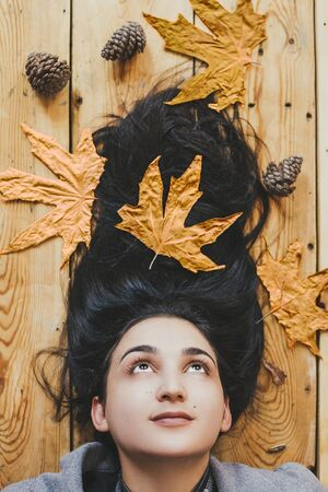 Autumn woman. Fall season concept. A portrait of lying on wooden floor woman. Young, beautiful and happy female holding a big yellow autumn leaf. View from above