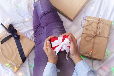 Christmas morning and a special gift for her. Present for Christmas from lover, husband or boyfriend. A woman has a surprise present for her in bed. Young female with Xmas gift box. Holiday surprise. Фото со стока - 131313051