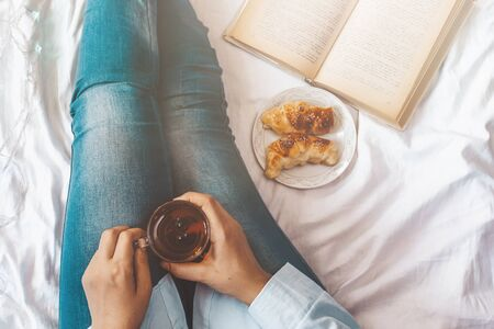 Winter holidays. Autumn morning. Woman having breakfast in bed. Coziness weekend morning. View from above to woman with teacup and croissants in bed. Relaxing Sunday activities Stock fotó