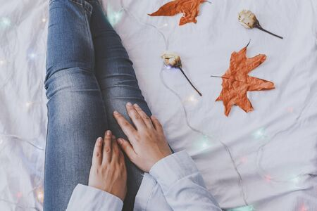 Cozy bedroom. Females relaxing at her bed in a cold autumn morning. Fall leaves and dried rose flowers. A woman dreaming and resting. Autumn Sunday. Top view. Happy weekend, Sunday activities
