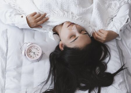 Beautiful black-haired woman sleeping in cozy bed. The alarm clock set at 7 a.m. morning. Female is going to wake up at 7 oclock early morning. Top view to cute and sweet female.