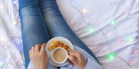 Winter holidays. Autumn morning. Woman having breakfast in bed. Coziness weekend morning. Woman with cup of coffee latte in hands, apples and croissants on bed. Relaxing Sunday activities. Top view