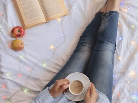 Woman on the bed with old book and cup of tea. Woman holding a book and tea in hands. Female reading book on bed in early weekend morning. Leisure time, cozy and soft photo of winter holidays at home Stock fotó