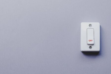 Light switch on grey wall. On and Off switch. Saving energy concept with copy space.