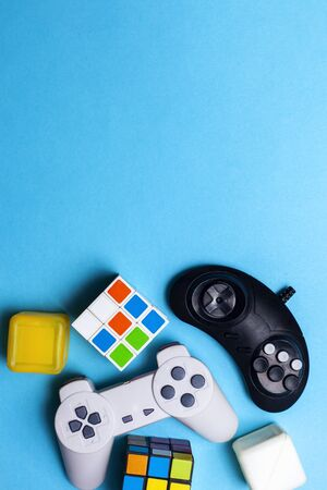Gaming background. Video console and board games elements on bright blue background. Miscellaneous gaming pieces. Copy space