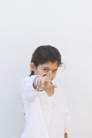 Annoyed girl saying its you, its the first time, pointing with her finger at the camera. Showing hand gesture this is you, you are chosen. Negative emotions. Unhappy little girl Reklamní fotografie