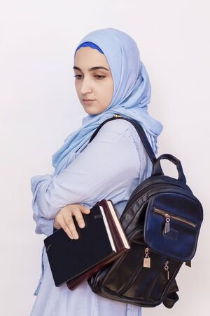 Modern Muslim student girl in hijab. Young middle-eastern college student with backpack holding books and notepads. Isolated on white background. Muslim student wearing traditional clothes