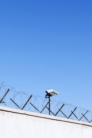 Security camera behind barbed wire fence stretched around prison walls. Security, surveillance camera watching area. Prison wall or highly protected government secret area, security concept 스톡 콘텐츠