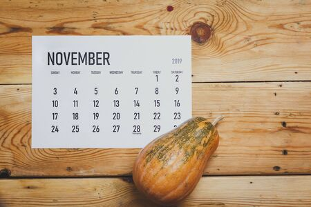 View from above to simple November 2019 calendar decorated with pumpkin