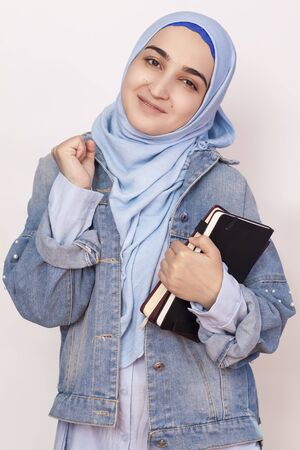 Happy Muslim businesswoman celebrating her first success in business. Attractive Muslim student holds notepads and celebrates successfully passed exams. Lovely stylish Muslim girl feels happy