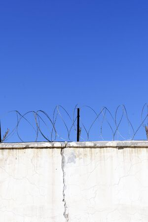 Jail wall. Highly protected prison wall with barbed wire fence. Blue sky background with copy space 스톡 콘텐츠