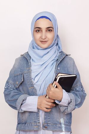 Portrait of cute Muslim businesswoman. Attractive Muslim student holding notepads. Lovely Muslim girl in traditional Islamic hijab and denim jacket. Modern, cultural, religious and business concept Stock Photo
