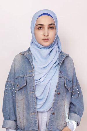 Modeporträt des stilvollen muslimischen Mädchens in der Jeansjacke. Modernes und junges Mädchen aus dem Nahen Osten, das Hijab mit Jeansjacke trägt. Mischung aus Kulturen. Traditionelle islamische und moderne westliche Kleidung Standard-Bild