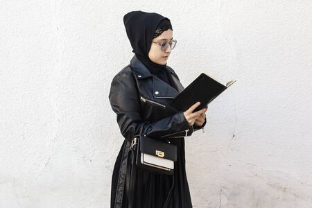 Young middle-eastern student girl holding in hands stack of notepads and her handbag. Modern Muslim woman wearing traditional Islamic clothing hijab and leather winter jacket