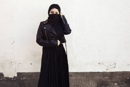 Beautiful Iranian girl in black dress and leather jacket. Attractive Muslim woman in hijab covering her face with a black scarf. Middle-eastern female in traditional Islamic clothing