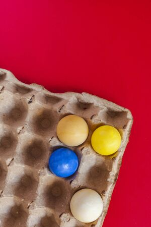 An egg carton with four pastel dye easter eggs on the red paper background. Vertical image. Happy Easter concept
