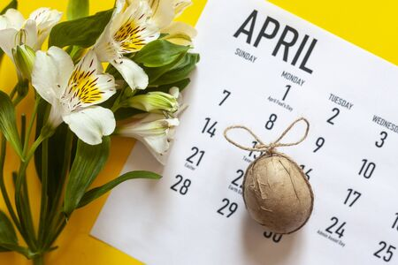 Happy Easter April 2020 Calendar colorful with an easter egg. Easter festive holidays concept. April 2020 monthly calendar with an easter egg on the bright yellow background. View from above
