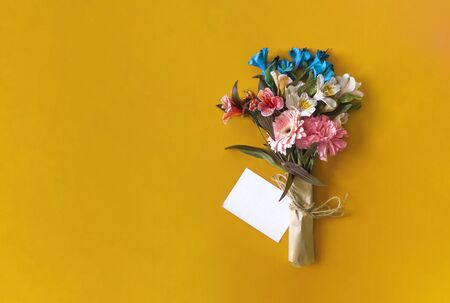 Colorful wild summer flowers. A bouquet of flowers with a blank white card on the yellow colored background. Top view of spring floral background with copy space