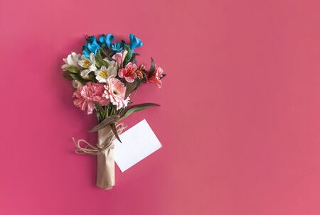 Spring flowers bouquet and greeting card. A bouquet on the bright pink background. Top view of spring floral background with copy space