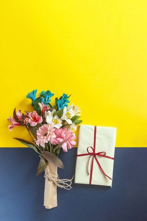 A colorful spring flowers bouquet with a present box on the multicolored paper background. Possible concepts of birthday, valentines day, anniversary, mothers day, wedding, love