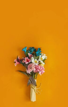 A bouquet of fresh spring flowers on the bright colored background. Top view of spring floral background with copy space