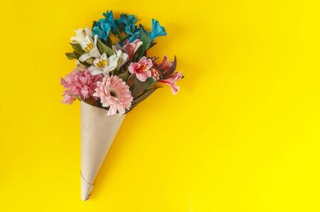 A bouquet of fresh spring flowers on the bright yellow background. Top view of spring floral background with copy space