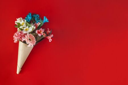 A bouquet of fresh spring flowers on the red background. Top view of spring floral background with copy space Foto de archivo