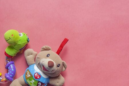 Toy for baby. Teddybear for baby on pink background. Top view. Copy space