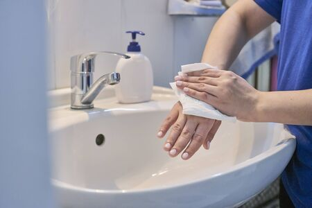 Close-up view of woman using soap and washing hands under the water tap in the bathroom. Personal hygiene to stop spreading coronavirus outbreak