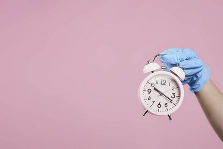 Time ticking bomb. Pandemic covid-19 outbreak. Hands in protective medical gloves holding an alarm clock. Coronavirus pandemic. Stay home, Stay safe. Work from Home concepts. Growing death deases Standard-Bild - 143948897