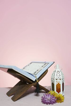 Quran open in wooden placemat. Holy month in the Muslim world - Ramadan Kareem. Eid-al-adha concept. Wooden Rehal with open holy book Quran and rosary beads. Arabic lantern colorful spring flowers Archivio Fotografico