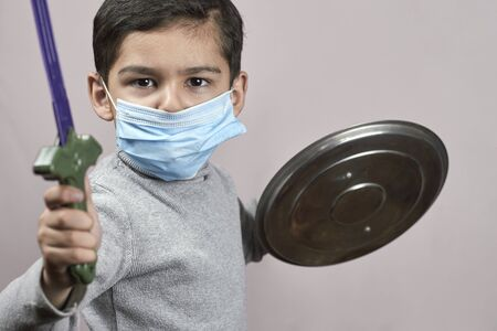 Bored boy in medical face mask plays knight cavalier. Little moddle-eastern kid in surgical masks having fun during covid-19 pandemic. Self-isolation and quarantine