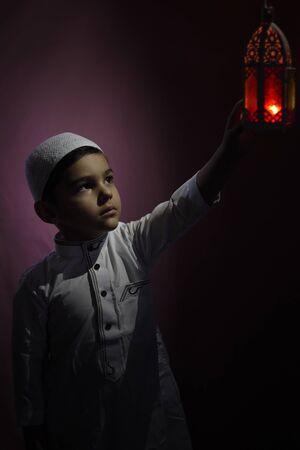 Muslim boy touching traditional Arabic lantern candle blowing in the dark. Middle-eastern boy praying. Thanking god. Ramadan, Eid-al-Adha concepts