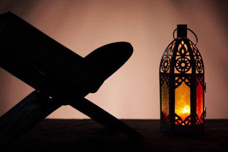 Ornamental Arabic lantern with burning candle glowing in dark and Holy Quran. Festive greeting card, invitation for Muslim holy month Ramadan Kareem Standard-Bild