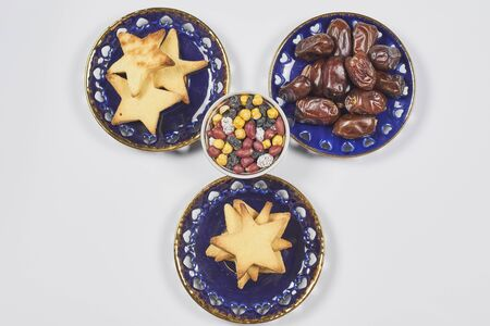 Traditional Ramadan dinner on pure white table. Traditional middle-eastern lunch with cookies and dry date fruits. Ramazan Iftar food - meal Muslims eat after sunset during Ramadan