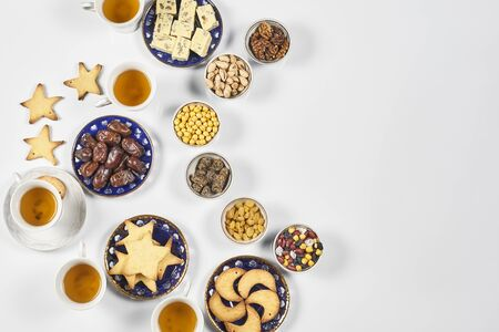 Traditional Ramadan dinner on pure white table. Traditional middle-eastern lunch with cookies and sweets. Ramazan Iftar food - meal Muslims eat after sunset during Ramadan. Top view