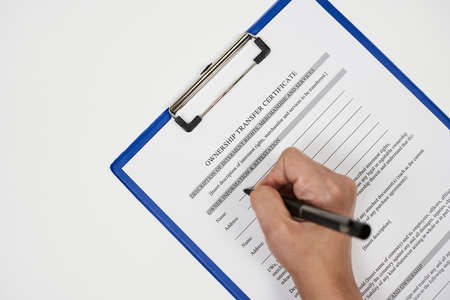 A person filling ownership transfer certificate document Stock Photo