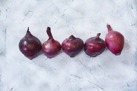 Fresh purple onions placed in the line. Top view