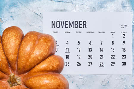 Simple November 2020 calendar decorated with pumpkins on bright background. View from above. Top view