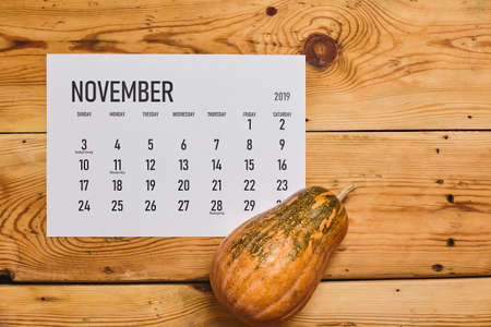 Simple November 2020 calendar decorated with pumpkins on wooden background. View from above. Top view