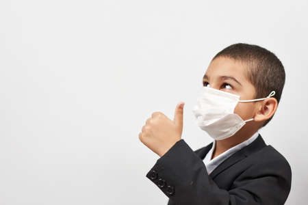Happy schoolboy in face mask. Mixed-race kid shows thumbs-up gesture between pile of books. Back to school after covid-19. School year start after long delay due to coronavirus Stock fotó