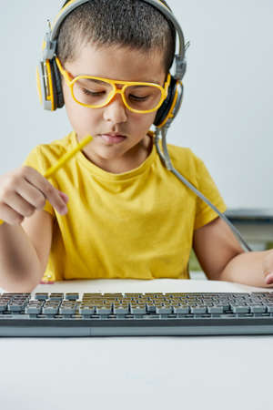 An adorable kid in a yellow t-shirt with a headphone listening online course. Boy typing on pc keyboard. Homeschooling. Cute mixed-race schoolboy learning a foreign language online