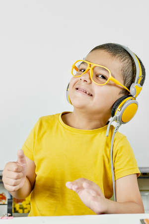 A mixed-race kid in yellow wearing headphones looking happy. Joyful schoolboy portrait. Back to school after the covid-19 pandemic