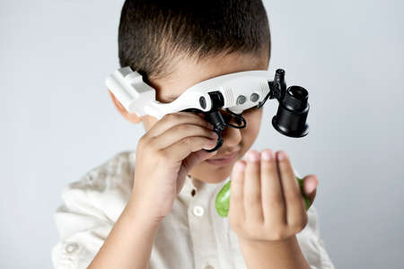 A boy in head magnifying glasses headset learning Incredible chemistry of slimes. Tactile play or sensory play for older kids 免版税图像