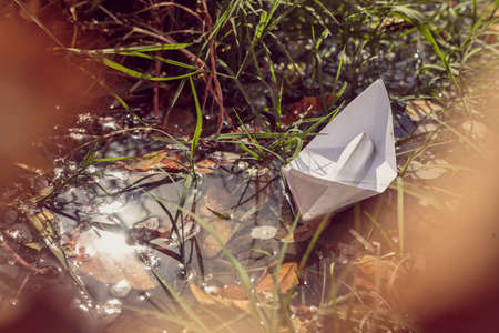 Origami paper boat sailing on the water. Autumn waters taking away all problems. Let your dreams set sail