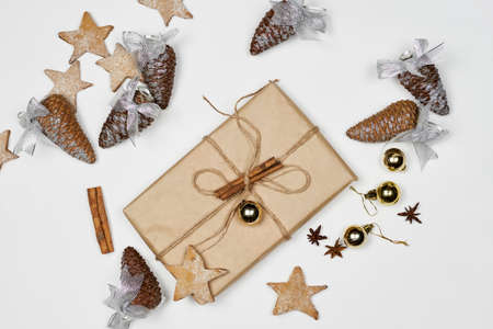 Xmas gift surrounded with decorated pine cones, sweet star shape cookies, cinnamon and Christmas ornaments