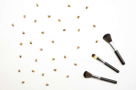 Cosmetic make-up brushes and golden trinkets on white background