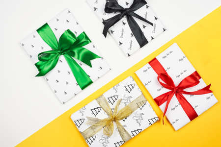 X-mas gift wrapped in paper with Christmas prints and tied with black ribbon. Christmas present box on white background