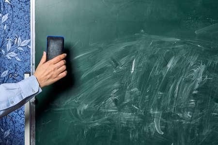 A teacher cleans a dirty green chalkboard Stock Photo